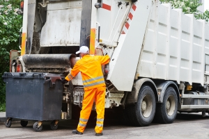 Worker of urban municipal recycling garbage collector truck load